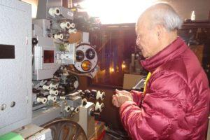 写真11 まち遺し深谷の代表で深谷シネマ館長でもある竹石研二さん 今はあまり使われなくなってしまった映写機とともに(著者撮影)