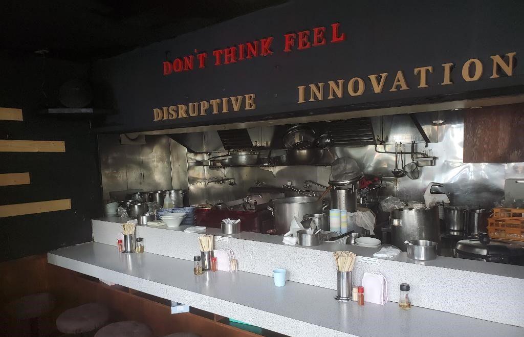 「破壊的イノベーション」の店内の様子。席を減らして営業している。「DON'T THINK FEEL」の文字には「一口食べた時に頭で考えるより全体で感じてほしい」という想いがこもる。(提供・破壊的イノベーション)