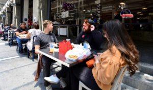 ロサンゼルス市内のレストランで食事をする人たち。再感染が広がりレストランやバーの営業が一部制限されている-ⓒAFP PHOTO /FREDERIC J. BROWN