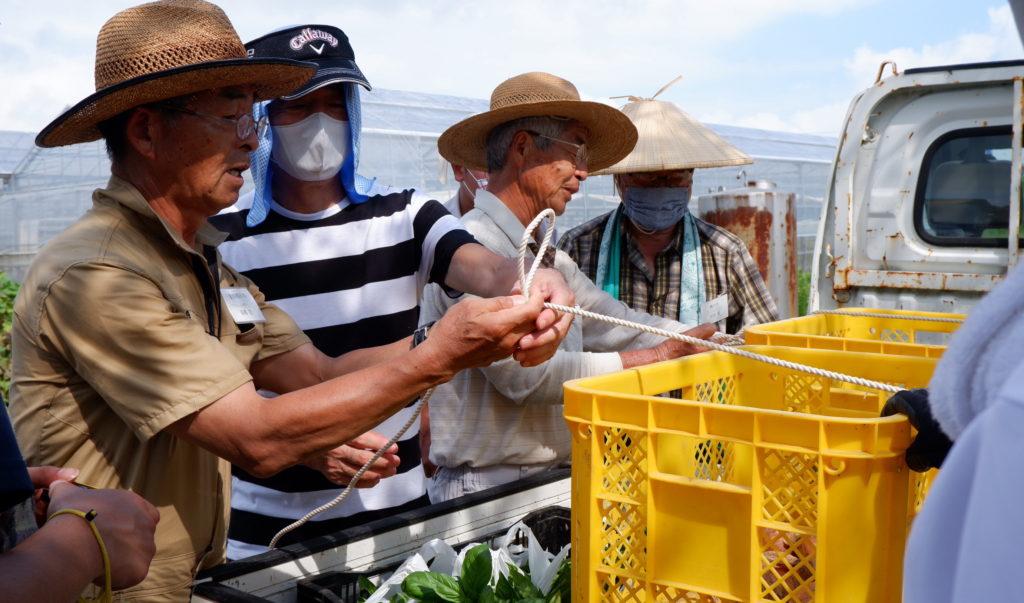 軽トラックの積荷の固定を参加者に教える先輩移住者の高橋稔さん(左)。