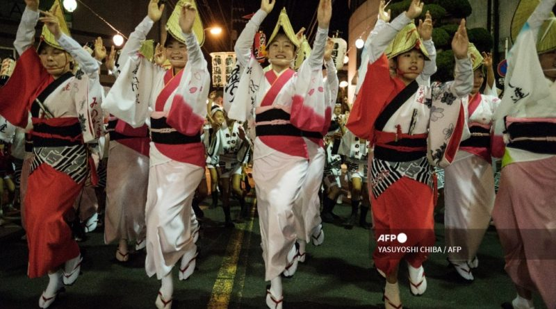"""This photo taken on August 16, 2017 shows dancers performing on a street at the Ikeda Awa Odori Festival in the city of Miyoshi, about 80 kms west of Tokushima, Tokushima prefecture, on Japan's Shikoku island. - Various places in Tokushima prefecture hold the annual Awa Odori festival during """"obon"""", an annual Buddhist period in August to welcome ancestors' souls which are believed to return to this world and visit their families. (Photo by YASUYOSHI CHIBA / AFP)"""