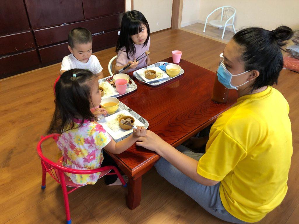 スタッフに手伝ってもらいながら夜ごはんを食べる子どもたち=2021 年6月23日、後藤陽佳撮影