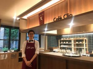 Café Clio店長の手串さん。カウンターの上には珈琲研究会のタペストリーがかかっている