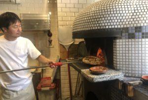 店内の薪釜でピザを焼く藤田さん。その眼差しは真剣そのものだ。
