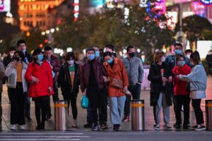 People wearing face masks amid concerns over the COVID-19 coronavirus outbreak walk along a shopping district in Shanghai on March 20, 2020. (Photo by Hector RETAMAL / AFP)