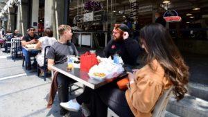 2020年7月1日、ロサンゼルス市内のレストランで食事をする人たち。感染が再拡大するカリフォルニアでは室内のレストランやバーの営業が一部制限されている= ⓒAFP PHOTO /FREDERIC J. BROWN