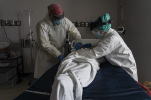 HOUSTON, TX - JUNE 30: (EDITORIAL USE ONLY) Medical staff wears full PPE as they wrap a deceased patient with bed sheets and a body bag in the Covid-19 intensive care unit at the United Memorial Medical Center on June 30, 2020 in Houston, Texas. Covid-19 cases and hospitalizations have spiked since Texas reopened, pushing intensive-care wards to full capacity and sparking concerns about a surge in fatalities as the virus spreads.   Go Nakamura/Getty Images/AFP