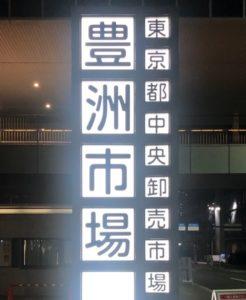 夜明けに光る豊洲市場の看板
