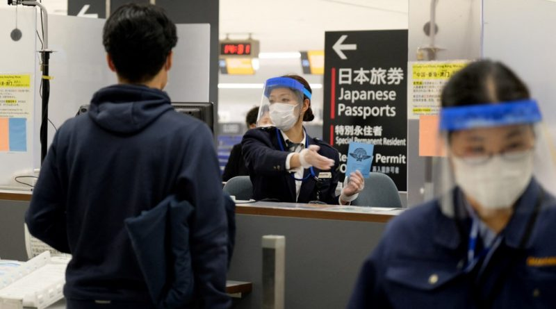 An officer wearing a face mask and shield gestures to a passenger arriving from Hong Kong, at a quarantine station at Narita airport, Chiba prefecture on March 9, 2020. - Japanese Prime Minister Shinzo Abe on March 5 announced that foreign arrivals who have recently been in China or South Korea would be required to spend 14 days in quarantine amid concerns of the COVID-19 novel coronavirus. (Photo by Kazuhiro NOGI / AFP)